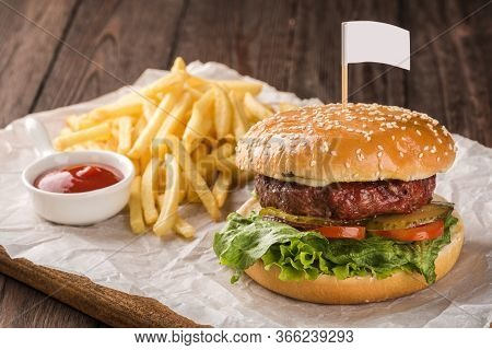 Beef Burger Served With French Fries And Tomato Ketchup.