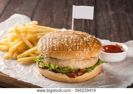 Chicken Burger On A Wooden Board. Served With French Fries And Tomato Ketchup.