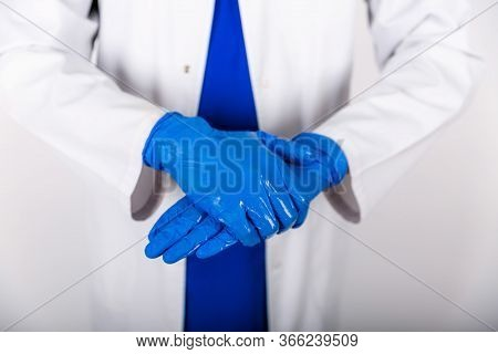 Treatment Of Blue Rubber Gloves With An Antiseptic Against Bacteria. The Doctor Uses An Antiseptic W