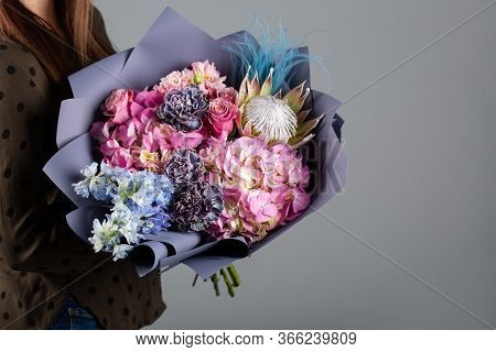 Beautiful Bouquet In The Hands Of A Florist. From Color Protea, Cloves And Hydrangeas To Brown Paper