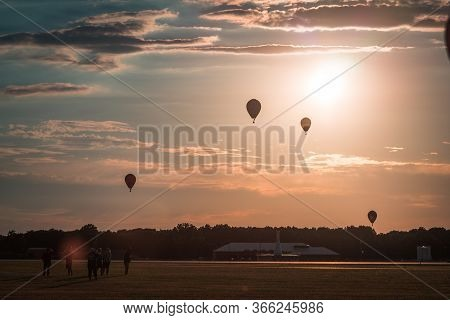 Hot Air Balloons Floating Through The Air At Sunset At An Airshow