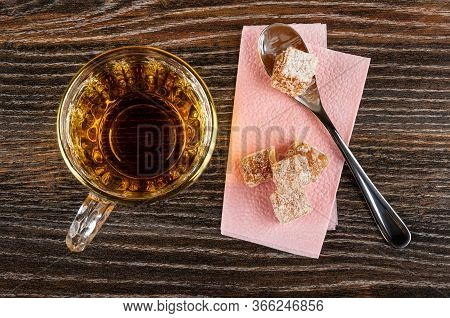 Transparent Cup With Tea, Teaspoon And Pieces Of Rahat-lokum On Paper Napkin On Dark Wooden Table. T