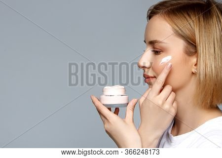 Close Up Woman Holding Bottle Of Cream In Hand And Apply It On Face With Finger. Skin Care, Moisturi