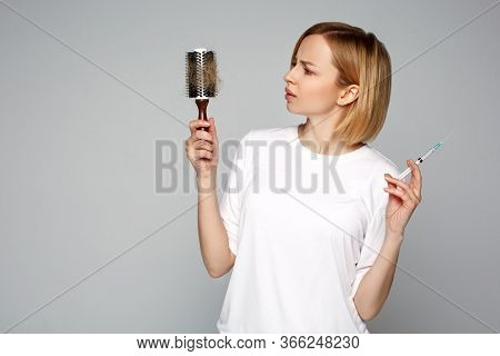 Close up woman holding syringe with mesotherapy injection and hairbrush in hand, choosing hair loss problem care product. Cosmetology and beauty industry. Benefits and side effects of procedure