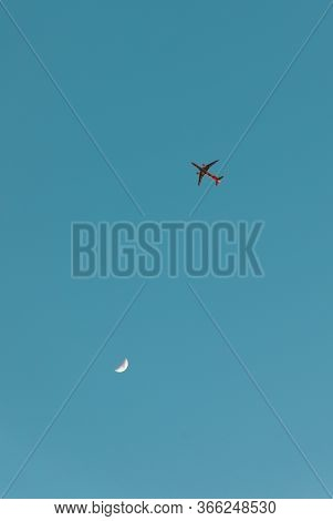 Plane And Crescent Moon Close Together On The Turquoise Sky