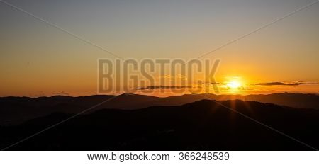 Beautiful Sunset With Sun Rays With Hills Silhouette And Copy Space