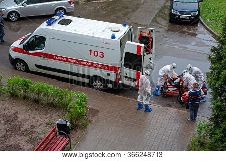 Minsk, Belarus - May 12, 2020: Team Of Medical Personnel In Protective Suits Hospitalizes Patient Du