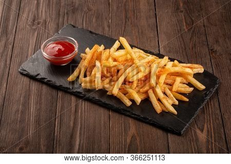 Fried Fries On A Stone Black Board, Served With Tomato Ketchup.