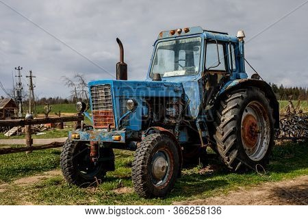 Blue Tractor On A Farm. Cloudy Sky On Background.