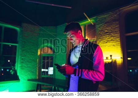 Message. Cinematic Portrait Of Stylish Man In Neon Lighted Interior. Toned Like Cinema Effects, Brig
