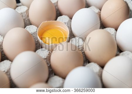 Chicken eggs in organic packaging closeup. Egg half broken among other eggs. Food photography