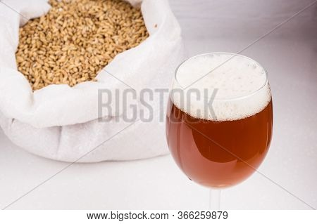 Bag Of Light Malt  And Glass Of Home Made Craft Beer A Wooden Table On White Background. Craft Beer