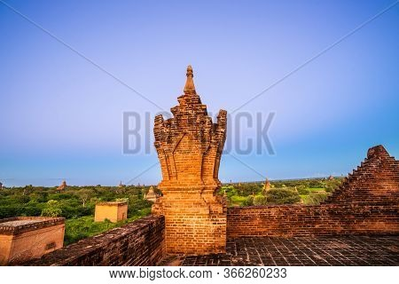 Looking From Top Of Brick Stupa With Imposing Minaret Over Green Landscape With Stupa Scattered Acro
