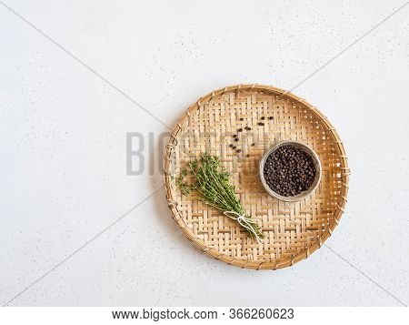 Kitchen Background With Wicker Tray. Black Pepper And Fresh Thyme On Light Background. Top View. Cop