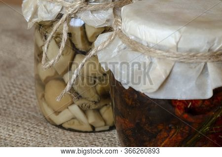 Jars Of Canned Food On Burlap. Two Glass Jars With Canned Mushrooms And Sun-dried Tomatoes. Ingredie
