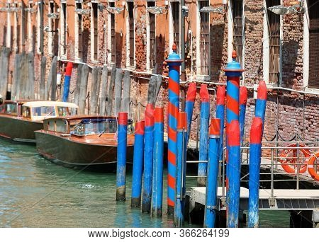 Some Boats And Poles Called Bricola In Italian Language To Moorings In The Grand Canal In Venice In