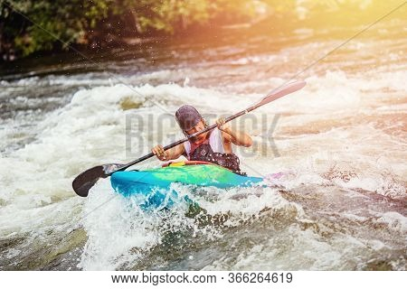 Guy In Kayak Boat Overcomes Threshold Of Mountain River, Boiling Water. Rafting Concept