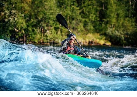 Extreme Sport Rafting Whitewater Kayaking. Guy In Kayak Sails Mountain River