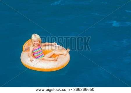 Photo Of Happy Child Swimming With Fun On Inflatable Floating Ring In Sea Water Pool. Family Travel