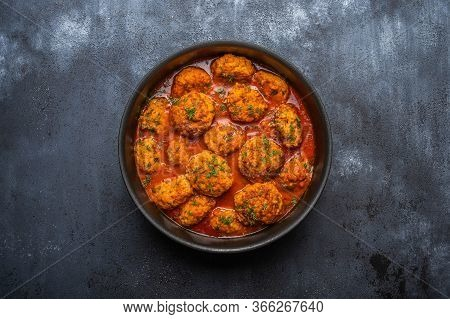 Homemade Meatballs In Tomato Sauce With Herbs In A Saucepan On A Dark Wooden Background. Top View