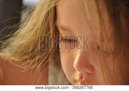 Teardrop On The Cheek Of A Little Girl.a Small, Sad, Upset Girl Crying A Tear Rolls Down Her Cheek.