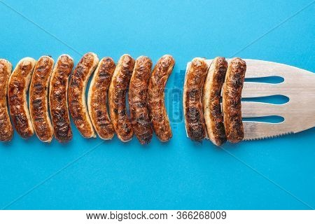 Above View With Grilled Bavarian Bratwurst On Blue Background. Delicious German Bratwurst