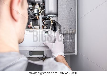 Close Up Of Caucasian Service Worker Fixing Central Heating Furnace System.
