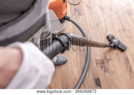 Close Up Of Man Cleaning And Vacuuming Hardwood Floor After Flooring Installation.