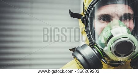 Close Up Of Caucasian Man Standing Observing And Wearing Hazmat Suit And Gas Mask.