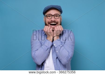 Excited Caucasian Man With Glasses And Blue Hat Being Excited Receiving Great News