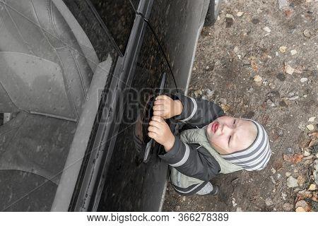 Cute Little Blond Boy In Striped Hat Struggles To Open Door Of Black, Dusty Car, Hanging On Handle.
