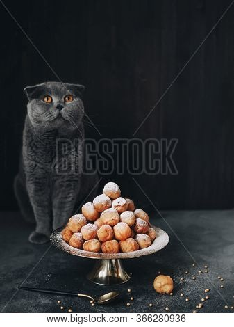 A Grey Scottish Cat Sits Next To A Pyramid Of Small Doughnuts. Doughnuts Are Small Yellow Balls In P