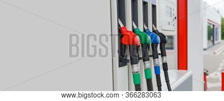 Various colored refueling pistols or fuel guns in fuel column on fuel station with copy space. Fuel guns installed in to nests.