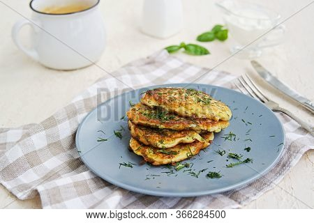Fritters Zucchini With Feta Cheese On A Gray Plate On A Light Concrete Background. Served With Sour