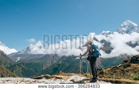 Young Hiker Backpacker Man With Trekking Poles Enjoying The Ama Dablam 6814m Peak Mountain During Hi