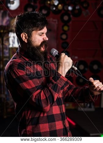 Man With Enthusiastic Face Holds Microphone, Singing Song,