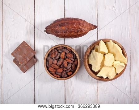 Broken Bar Of Milk Chocolate, Cocoa Pod, Cocoa Butter And Cocoa Beans On Light Wooden Background. To