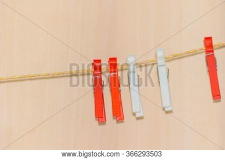 Pink Clothespins On A Wicker Rope. Plastic Clothespins For Drying Clothes.