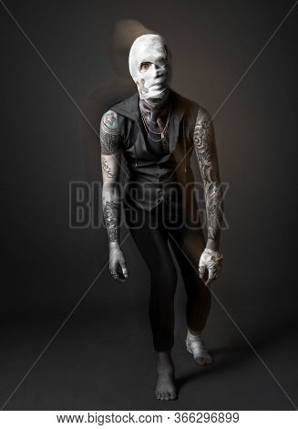 Injured, Strange Looking Man In Black Vest And Pants, His Arms Covered With Tattoos, His Head, Hand