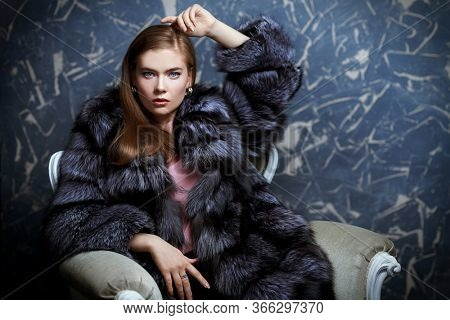Beautiful fashionable woman posing in a luxurious fur coat in a vintage armchair. Studio fashion shot.