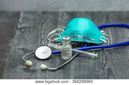 A Blue Medical Stethoscope, Face Mask Respirator, Syringe And Vial Of Covid-19 Test Vaccine On A Woo