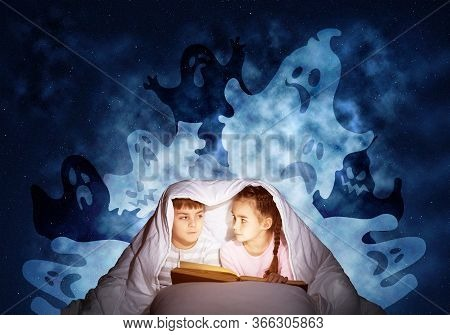 Cute Girl And Boy Reading Kids Book In Bed. Children With Flashlight Lying Under Blanket Together. K