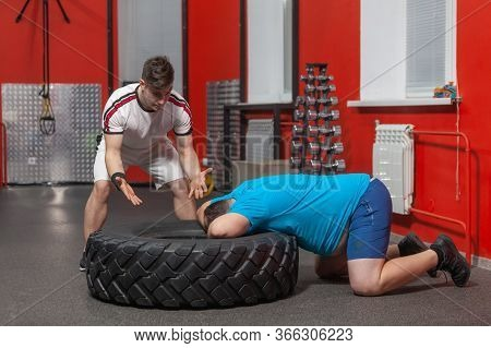 Personal Trainer Is Dissatisfied With His Overweight Sportsman Who Is Lying Exhausted With His Head