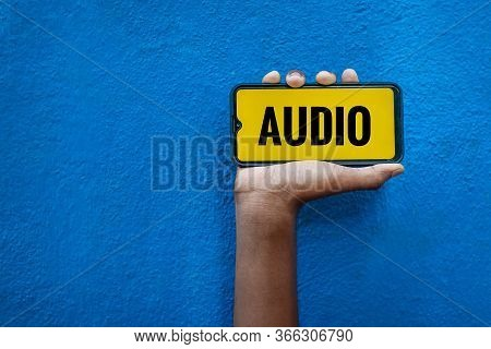 Audio Word On Smart Phone Screen Isolated On Blue Background With Copy Space For Text. Person Holdin