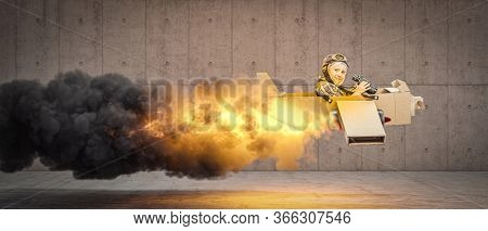 little boy plays to be an aviator on a cardboard plane, flames and smoke from the back. Face happy and smiling. concept of light-heartedness, aspirations, imagination.
