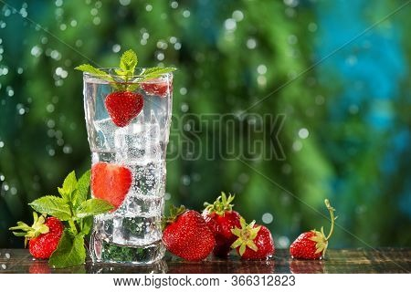 Refreshing Carbonated Drink With Many Strawberries And Ice Cubes, Against A Background Of Greenery A
