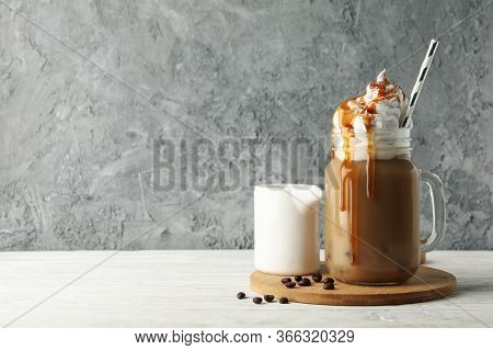 Iced Coffee With Poured Cream On White Wooden Background