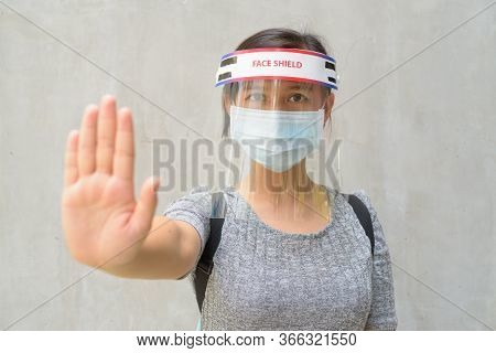 Young Asian Woman Showing Stop Gesture With Mask And Face Shield For Protection From Corona Virus Ou