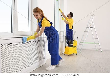 Professional Janitors In Uniform Cleaning Spacious Room