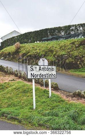 City Sign Santo Antonio De Nordestinho In Sao Miguel Island, Azores, Portugal. Rural Road On The Hil